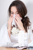 Ill woman blowing her nose in her living room Royalty Free Stock Photo
