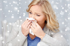 Ill woman blowing nose to paper napkin. Health care, flu, hygiene and people concept - ill woman blowing nose to paper napkin over snow Stock Images