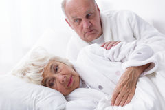 Ill woman and caring partner. Photo of ill old women in bed and caring partner Royalty Free Stock Photography
