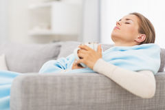 Ill woman with cup of hot beverage sitting on couch Stock Photo