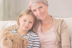 Ill woman embracing child. Ill women with headscarf embracing her small child Royalty Free Stock Images