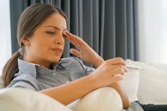 Ill woman with fever and colds looking a thermometer sitting on a sofa. Royalty Free Stock Photography
