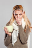 Ill woman holding a mug of tea and coughs Royalty Free Stock Images