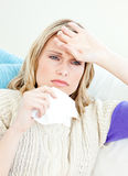 Ill woman holding a tissue sitting on a sofa Royalty Free Stock Image