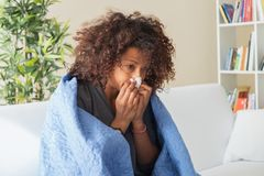 Sick black woman at home blowing her nose royalty free stock photos