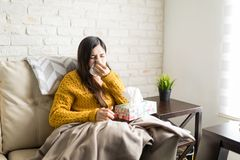 Ill Woman Sneezing At Home. Sick woman blowing her nose in tissue while sitting on sofa at home stock photos