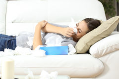 Ill woman sneezing in tissue flu concept. Ill woman sneezing in a tissue lying on a couch at home. Flu concept Royalty Free Stock Photos