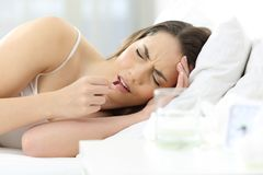 Ill woman taking a painkiller pill on the bed at home. Ill woman suffering headache taking a painkiller pill on the bed at home Stock Image