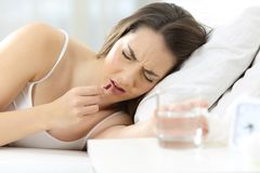 Ill woman taking pill lying on a bed. Ill woman taking a painkiller pill lying on a bed at home Stock Photos