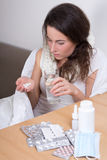 Ill woman taking pills in her living room Stock Photos