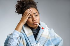 Ill woman with thermometer in her mouth, wrapped in plaid. Photo of african american woman wrapped in paid on gray background. Healthcare concept stock images