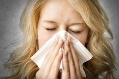Ill woman with tissue is sneezing Royalty Free Stock Image