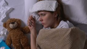 Ill woman with towel on forehead and runny nose hugging teddy bear in bed, flu