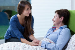 Ill woman. Ill women in bed talking with young pretty girl stock photos