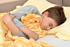 Ill young boy lying in bed                                 6198. Ill cute young boy with closed eyes lying in bed royalty free stock image