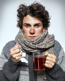 Ill young man with red nose, scarf, sneezing into handkerchief. Stock Photo