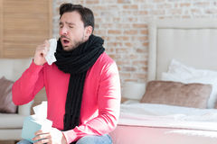 Ill young man sneezing. Flu epidemics. Sick unhappy bearded man holding a paper tissue and sneezing while sitting on the bed Stock Photo