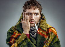 Ill young man with a thermometer in his mouth wrapped in plaid Royalty Free Stock Photo