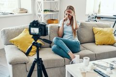 Ill young woman. Blowing nose while making social media video at home stock photography