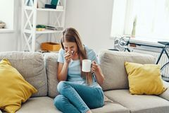 Ill young woman. Blowing nose and sneezing while sitting on the sofa at home royalty free stock photography