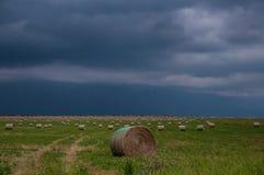 Illavarslande himmel med baler av hö Arkivfoto