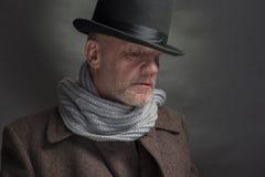 Illavarslande man som bär en bästa hatt och en grå halsduk royaltyfri foto