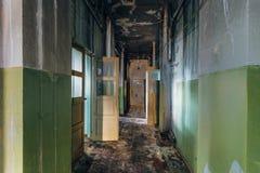 Illavarslande och kuslig korridor av det övergav sjukhuset efter brand Tak i svart sot royaltyfri foto