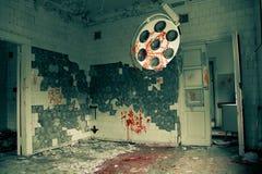 Illavarslande och kusligt övergett fungeringsrum i sjukhuset royaltyfri foto