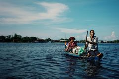 local family crossing the lake on his canoe in front of the floating stilt house settlement stock photo