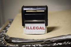 Illegal concept stamp on a big folder of paperwork. Illegal word on a stamp on a big folder of paperwork royalty free stock images