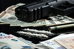 Illegal drugs , money and guns. Close up shot of cocaine, US dollars, euros, pounds and a gun, on black background Royalty Free Stock Photo