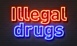 Illegal drugs neon sign on brick wall background. Royalty Free Stock Photography