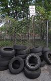 Illegal Dumping. This is a pile of used tires illegally dumped behind a business in front of a posted no dumping sign Stock Image
