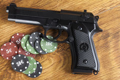 Illegal gambling concept of handgun with betting chips. Illegal gambling concept handgun with betting chips Royalty Free Stock Images