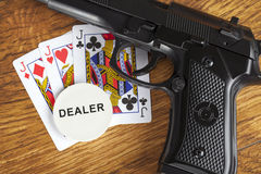 Illegal gambling concept with a handgun and poker hand and dealer chip Royalty Free Stock Image
