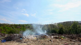 Illegal garbage dump - trash burning outdoors. HD 1080 static: Illegal garbage dump - trash burning outdoors; various waste making land and air pollution stock video footage