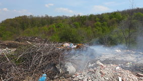 Illegal garbage dump - trash burning outdoors. HD 1080 static: Illegal garbage dump - trash burning outdoors; various waste making land and air pollution stock video