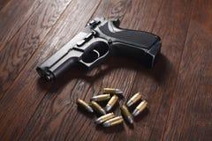 Illegal handgun on wooden table. Illegal handgun with cartridges on wooden table 9mm barrel black firearm gray grip guard magazine metal parabellum pistol royalty free stock photos