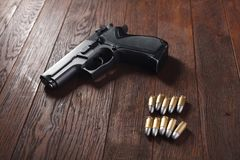 Illegal handgun on wooden table. Illegal handgun with cartridges on wooden table 9mm barrel black firearm gray grip guard magazine metal parabellum pistol royalty free stock photography