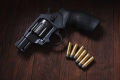 Illegal handgun on wooden table. Illegal handgun with cartridges on wooden table 9mm barrel black firearm gray grip guard magazine metal parabellum pistol royalty free stock image