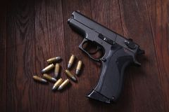 Illegal handgun on wooden table. Illegal handgun with cartridges on wooden table 9mm barrel black firearm gray grip guard magazine metal parabellum pistol stock photo