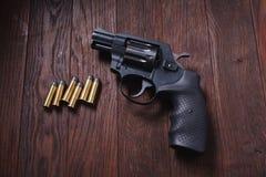 Illegal handgun on wooden table. Illegal handgun with cartridges on wooden table 9mm barrel black firearm gray grip guard magazine metal parabellum pistol royalty free stock images