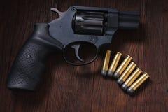 Illegal handgun on wooden table. Illegal handgun with cartridges on wooden table 9mm barrel black firearm gray grip guard magazine metal parabellum pistol royalty free stock photo