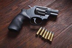 Illegal handgun on wooden table. Illegal handgun with cartridges on wooden table 9mm barrel black firearm gray grip guard magazine metal parabellum pistol stock photography