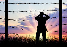 Illegal immigration of refugees. Silhouette of a broken border fence and border guards Royalty Free Stock Images