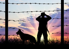 Illegal immigration of refugees. Silhouette of a broken border fence and border guards with a dog stock image