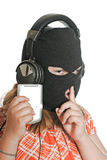 Illegal MP3 Downloads. Closeup view of a young girl wearing a ski mask, listening to illegal music, isolated against a white background stock photography