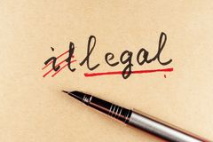 Illegal to legal. Amending Illegal word and changing it  to legal using a pen Stock Photos