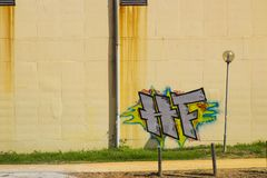 Illegale Graffiti auf einem Rost befleckten Wand eines Gebäudes in Albuferia in Portugal Lizenzfreies Stockfoto