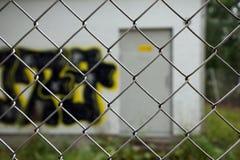Illegale Graffiti hinter einem Zaun Stockfotos